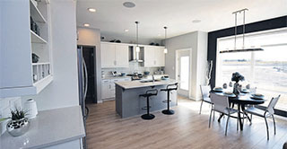 Looking into the kitchen from the great room inside our show home, the Brunswick, at 331 Tanager Trail in Sage Creek