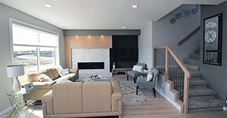 Great room with marble fireplace surround and stairs leading up to the second level inside our show home, the Brunswick, at 331 Tanager Trail in Sage Creek